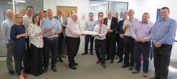 Peter Tresadern from INX International (pictured middle left) and Andy Clifton of Domino (pictured middle right), unveil the ceremonial plaque and birthday cake at the 25 year celebration